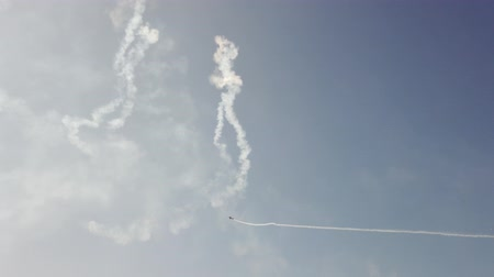 aerobatic : An airplane in the sky shows aerobatics figures