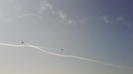 アクロバティック : Airplanes flying on the background of blue sky and leaving a condensation trail. 4K