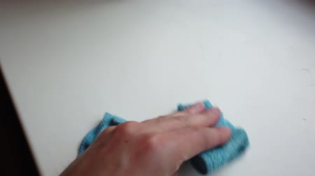 уборка : Mans hand with rag wipes dust from the windowsill.