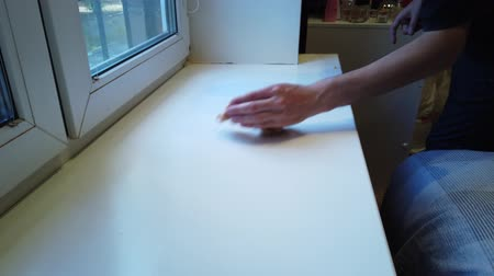 sanitize : Mans hand with rag wipes dust from the windowsill.