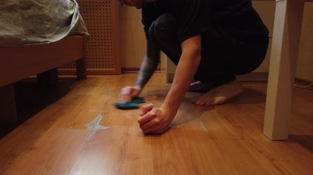 mopping : Young man washing floor at home. Closeup of a mans wiping dirt from a wooden floor with a special cloth.