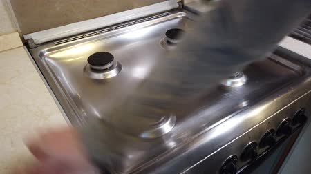 dienstbode : Cleaning the stove in the home kitchen. Housekeeping concept. Hand with sponge washing the stove, close up Stockvideo