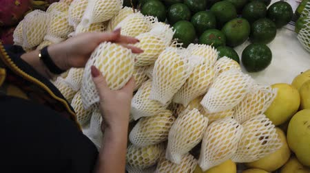 manga : Sale tropical Vietnam fruits on the counter of the market. Girl chooses exotic fruits in the store. Stock Footage