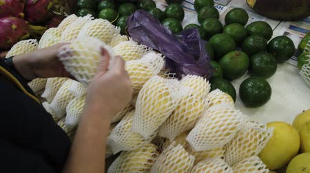 ananas : Sale tropical Vietnam fruits on the counter of the market. Girl chooses exotic fruits in the store. Dostupné videozáznamy