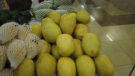 barato : Sale tropical Vietnam fruits on the counter of the market. Girl chooses exotic fruits in the store. Vídeos