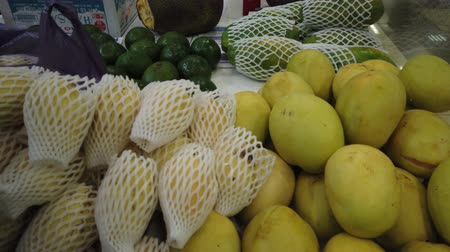 ananas : Sale tropical Vietnam fruits on the counter of the market. Girl chooses exotic fruits in the store. Stok Video