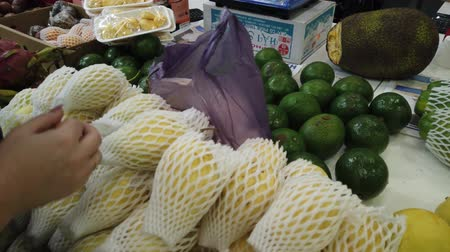 pronto : Sale tropical Vietnam fruits on the counter of the market. Girl chooses exotic fruits in the store. Vídeos