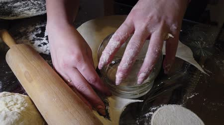 pelmeni : Rolling out the dough with a rolling pin on the kitchen table in a thin cake for making dumplings Stock Footage