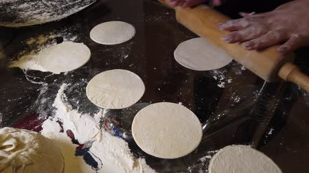 клецка : Rolling out the dough with a rolling pin on the kitchen table in a thin cake for making dumplings Стоковые видеозаписи