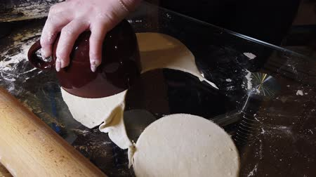 pasta maken : Woman adds some flour to dough on table. Step by step cooking homemade dumplings guide.