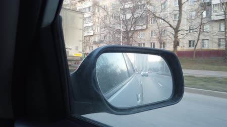 hátsó megvilágítású : The view from the rearview mirror is of the car. Driving through the busy city streets.