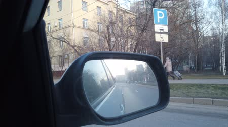mirror glass : The view from the rearview mirror is of the car. Driving through the busy city streets.