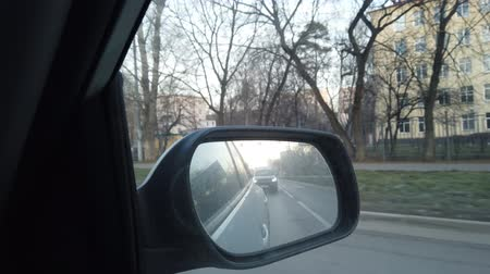 hátsó megvilágítású : The view from the rearview mirror is of the car. Driving through the busy city streets. The view from the rearview mirror is of the car. Driving through the busy city streets.
