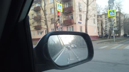 orta hava : The view from the rearview mirror is of the car. Driving through the busy city streets.