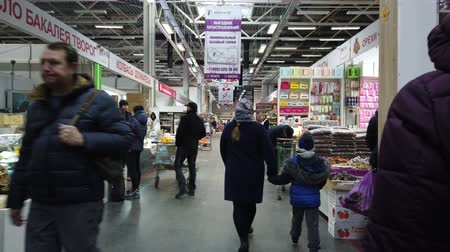 раздел : MOSCOW, RUSSIA - NOVEMBER 23, 2019: People walk around the supermarket in search of the right products. People in the food market.