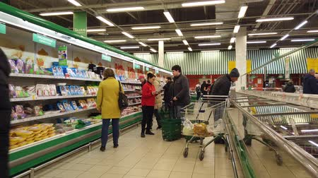 troli : MOSCOW, RUSSIA - NOVEMBER 23, 2019: People walk around the supermarket in search of the right products. People in the food market.
