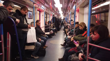 train tunnel : MOSCOW, RUSSIA - DECEMBER 12, 2019: People in the subway car. Moscow metro. Passengers sit in places with different activities. Stock Footage