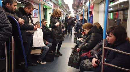 metropolitní : MOSCOW, RUSSIA - DECEMBER 12, 2019: People in the subway car. Moscow metro. Passengers sit in places with different activities. Dostupné videozáznamy