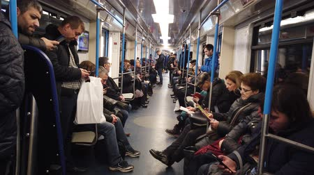 obyčejný : MOSCOW, RUSSIA - DECEMBER 12, 2019: People in the subway car. Moscow metro. Passengers sit in places with different activities. Dostupné videozáznamy