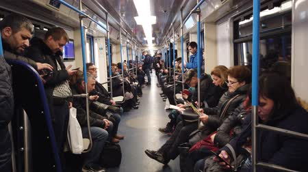 rendes : MOSCOW, RUSSIA - DECEMBER 12, 2019: People in the subway car. Moscow metro. Passengers sit in places with different activities. Stock mozgókép
