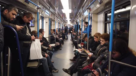 kombi : MOSCOW, RUSSIA - DECEMBER 12, 2019: People in the subway car. Moscow metro. Passengers sit in places with different activities. Videos