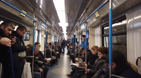 antrenör : MOSCOW, RUSSIA - DECEMBER 12, 2019: People in the subway car. Moscow metro. Passengers sit in places with different activities. Stok Video