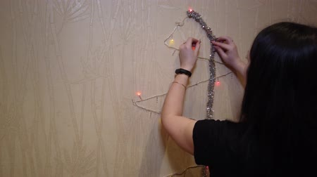 кукла : Christmas garland in the hands of a young woman creating an improved Christmas tree.