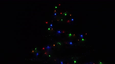improvised : A close up of LED string lights decorations. Festive LED light bulbs shining on improvised Christmas tree.