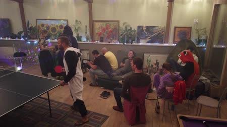 коттедж : NEMCHINOVKA, MOSCOW REGION, RUSSIA - JANUARY 01, 2020: A large group of friends celebrates the new year in the cottage, play table tennis and smoke hookah