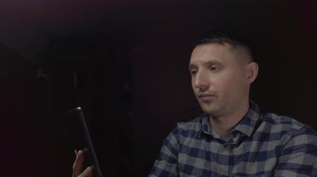Blogger man sitting in dark room broadcasts online on the tablet