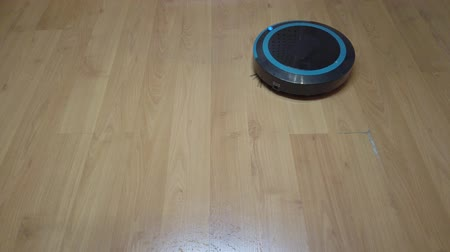 camera move : Robot vacuum cleaner rolls on laminate in the room
