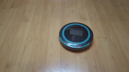 laminát : Robot vacuum cleaner rolls on laminate in the room