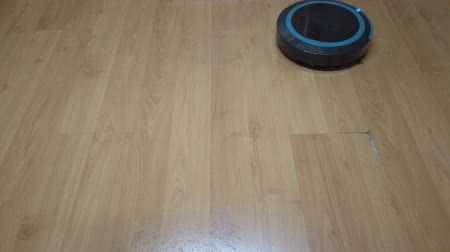 conveniência : Robot vacuum cleaner rolls on laminate in the room