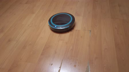 laminát : Robot vacuum cleaner rolls around the house, cleaning the house using electronics