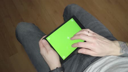 A man uses a tablet. Green screen on tablet