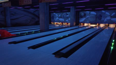 balanced : People play bowling, throw balls on the road of bowling