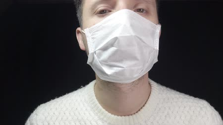 gripe : A man in a protective mask coughs. The man is sick, colds, cough.