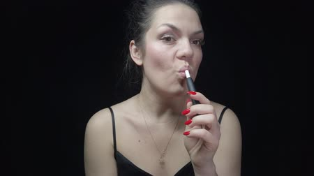 cigar : Close-up pretty woman with electronic cigarette. Young woman smoking tobacco stick heating and exhailing smoke.