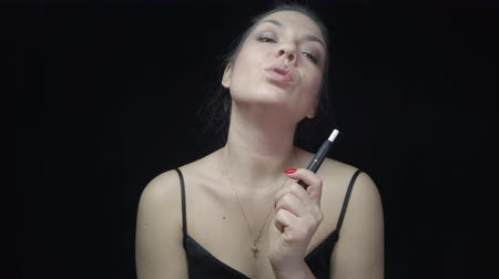 melez : Close-up pretty woman with electronic cigarette. Young woman smoking tobacco stick heating and exhailing smoke.