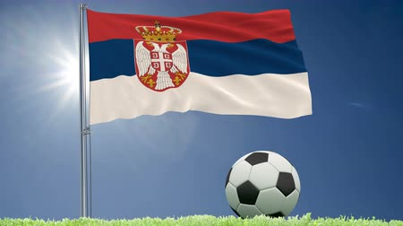 yugoslavia : Flag of Serbia fluttering and a football rolls on the lawn, 3d rendering, 4k footage