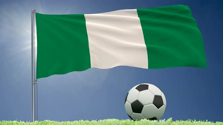 nigeria : Flag of Nigeria fluttering and a football rolls on the lawn, 3d rendering, 4k footage Stock Footage