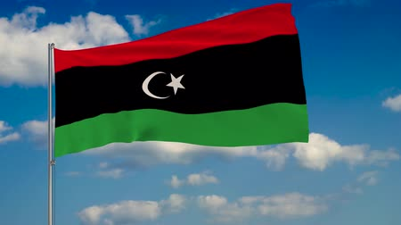 libya : Flag of Libya against background of clouds floating on the blue sky. Stock Footage