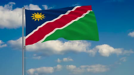 földrajz : Flag of Namibia against background of clouds floating on the blue sky.