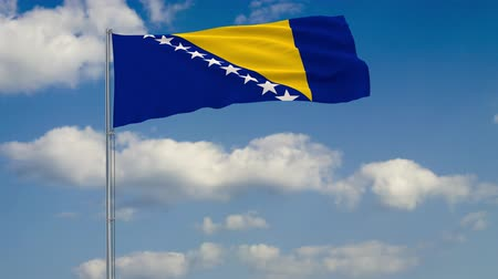 herzegovina : Flag of Bosnia and Herzegovina against background of clouds floating on the blue sky. Stock Footage