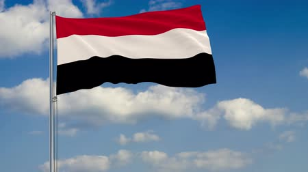 yemen : Flag of Yemen against background of clouds floating on the blue sky.