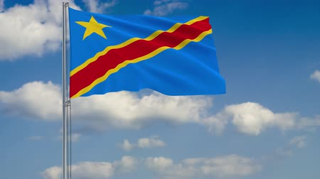 флагшток : Flag of Democratic Republic of Congo against background of clouds floating on the blue sky.