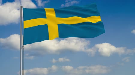 estocolmo : Flag of Sweden against background of clouds floating on the blue sky.