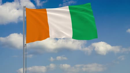 слоновая кость : Flag of Cote d Ivoire - Ivory Coast against background of clouds floating on the blue sky