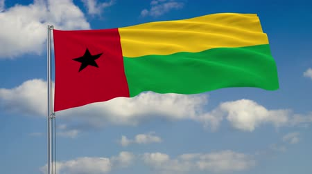 стандарт : Flag of Guinea-Bissau against background of clouds floating on the blue sky