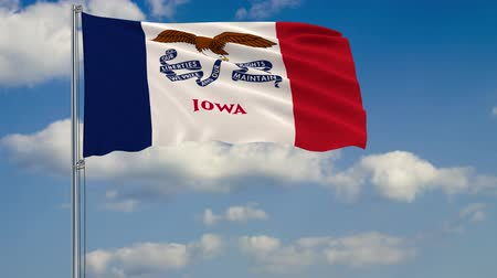 iowa : Flag of Iowa - US state fluttering in the wind against a cloudy sky Stock Footage